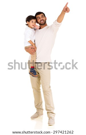 young indian father and son pointing at empty space on white background - stock photo