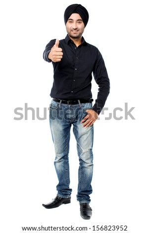 Young Indian guy showing thumbs up - stock photo