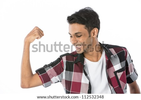 Young Indian man flexing his bicep. Isolated on white background.