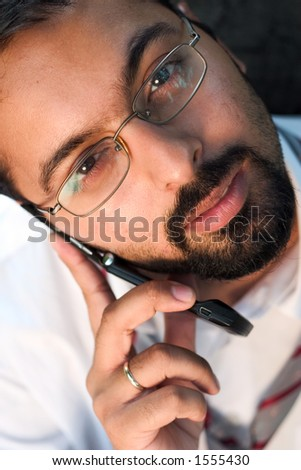 Young Indian man talking on a phone.