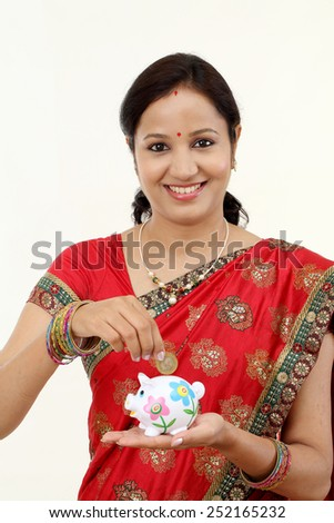 Young Indian traditional woman inserting coin in piggy bank - stock photo