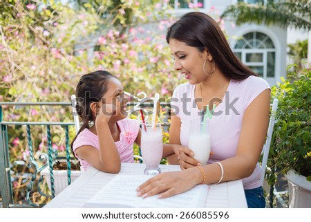 Young Indian woman and daughter talking and drinking cocktails - stock photo