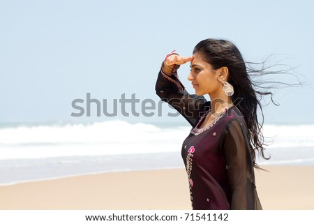 young indian woman at the beach looking at ocean - stock photo