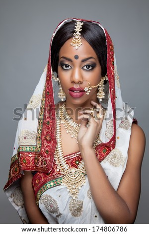 Young Indian woman dressed in traditional clothing with bridal makeup and jewelry