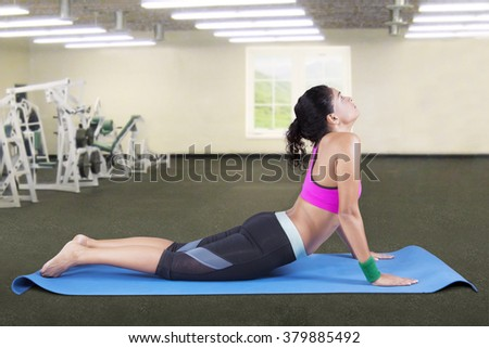 Young indian woman exercising cobra yoga pose in fitness center - stock photo