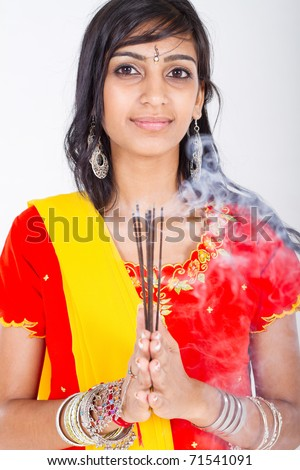 young indian woman holding incense, studio portrait - stock photo