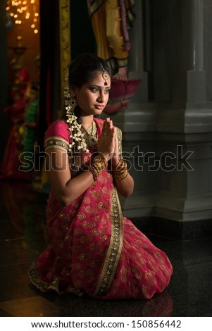 Young Indian woman in traditional sari dress praying in a hindu temple. - stock photo