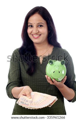 Young Indian Woman Saves Money in Piggy bank - stock photo