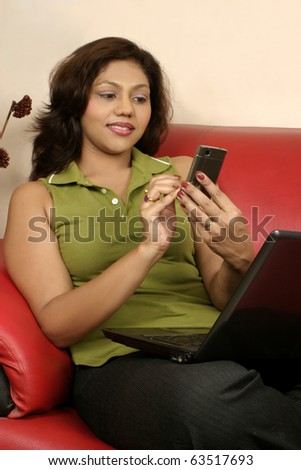 young Indian woman using touch screen phone - stock photo