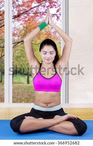 Young indian woman wearing sportswear and doing meditating on the mattress at home with autumn background on the window - stock photo