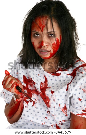 Young Indonesian woman covered in blood in hospital gown with knife. - stock photo