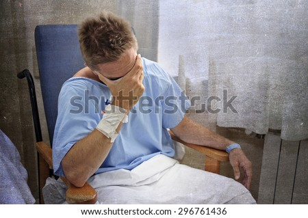 young injured man crying in hospital room sitting alone in pain looking negative and worried for his bad health condition sitting on chair suffering depression on a grunge medical background - stock photo