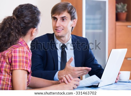 young insurance agent and customer discussing agreement terms and smiling - stock photo