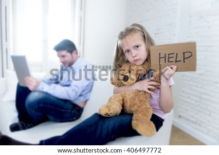 young internet addict father using digital tablet pad ignoring little sad daughter looking bored hugging teddy bear abandoned and disappointed with her dad asking for help - stock photo
