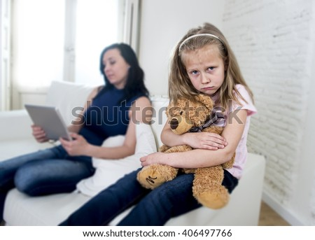 young internet addict mother using digital tablet pad ignoring little sad daughter looking bored hugging teddy bear abandoned and disappointed with her mum sitting on couch sofa - stock photo