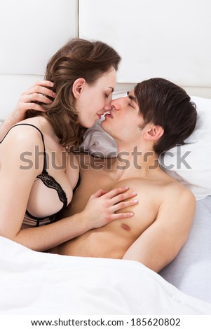 Young intimate couple kissing each other in bed at home - stock photo