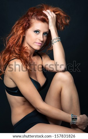 Young intimate redhead woman beauty portrait against black background.