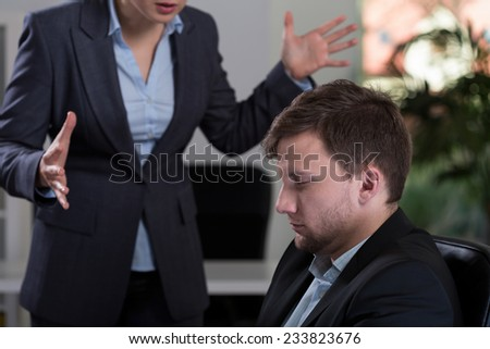 Young irate female boss and her fightened employee - stock photo