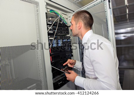 Young IT consultant working in a server room - stock photo