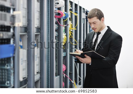 young it engeneer business man with notebook  in network server room - stock photo