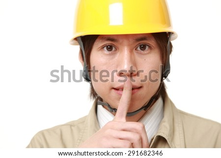 young Japanese construction worker whith silence gestures