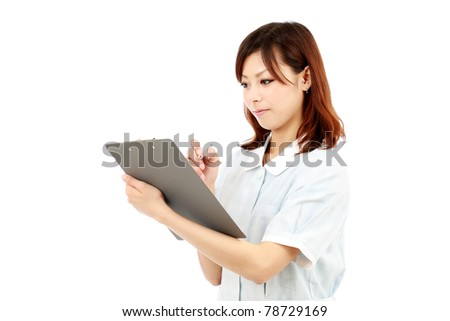 Young japanese female nurse in uniform, holding clipboard - stock photo