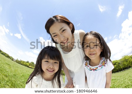 Young Japanese woman and two girls smiling in meadow - stock photo