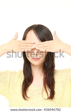 young Japanese woman covering her face with hands  - stock photo