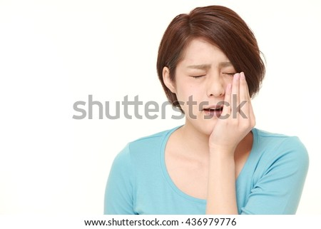 young Japanese woman in a blue shirts suffers from toothache - stock photo