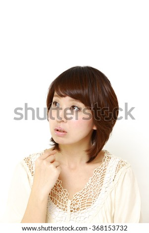 young Japanese woman thinks about something  - stock photo