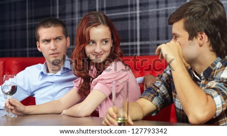 Young jealous angry man looking at his girlfriend sitting in a restaurant - stock photo
