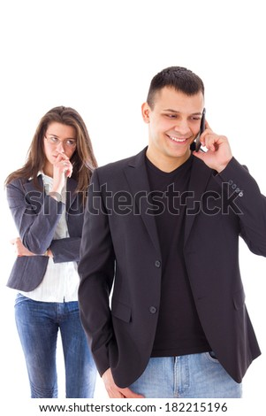 young jealous woman looking at her partner chatting on the phone - stock photo