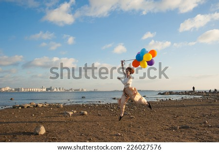 young Jennie jumping on the beach with balloons