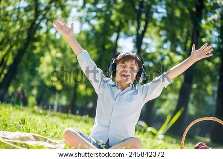 Young joyful boy in summer park wearing headphones - stock photo