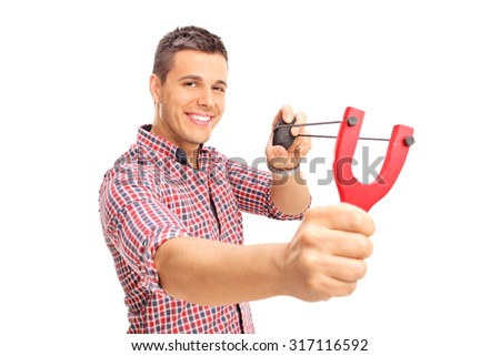 Young joyful guy shooting a rock from a slingshot and looking at the camera isolated on white background