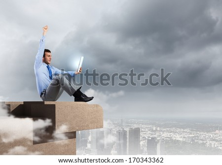 Young joyful handsome businessman using tablet pc