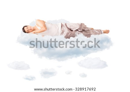 Young joyful man in pajamas sleeping on a cloud and dreaming isolated on white background - stock photo