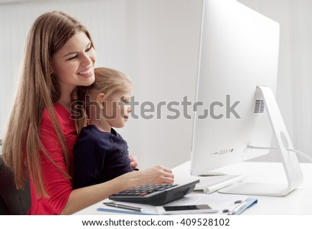 Young joyful mother calculating family budget sitting with her daughter at the desk. Concept of investment and banking.  - stock photo