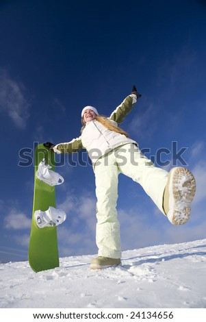 Young joyful snowboarder woman at mountains - stock photo