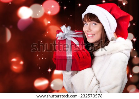 Young joyful woman in Santa's cap and  gloves keeps Christmas gift wrapped in red paper, on blurred background with shines light and particles - stock photo