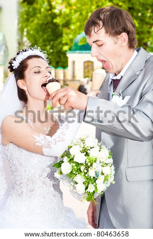 Young just married couple feeding each other with ice cream - stock photo