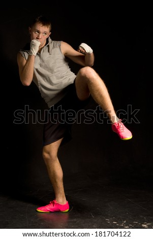 Young kickboxer ready to throw a punch while balancing on one leg with the other raised in a kick on a dark background - stock photo