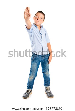 Young kid doing stop sign over white background  - stock photo