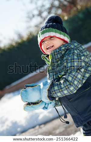 Young kid having fun in the snow with snowball. - stock photo