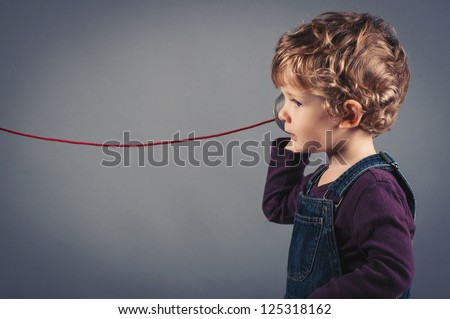 Young kid listen to tin can telephone. - stock photo