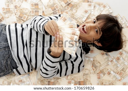 Young kid lying down in brazilian currencies .