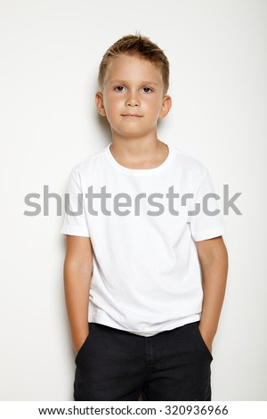 Young kid on the white background and wearing white tshirt and black shorts - stock photo