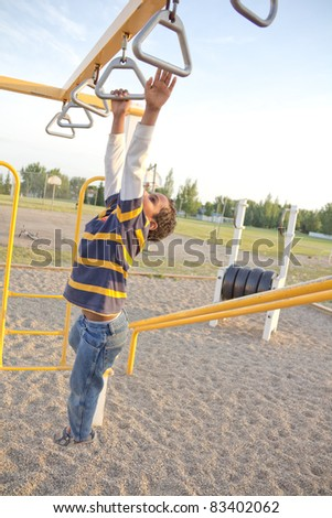 young kid playing at the playground stretching his hands to hang on the next bar - stock photo