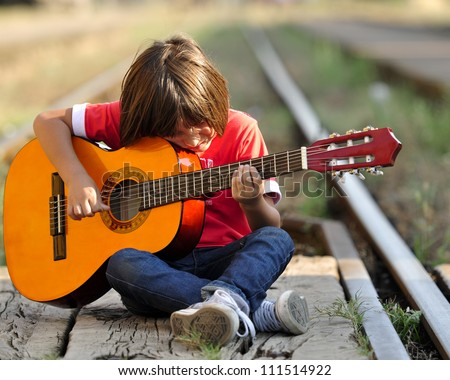 young kid playing guitar and sitting on railroad - stock photo