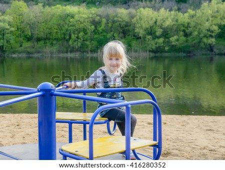 young kid playing on a blue merry-go-round on a sandy beach alongside a lake as they enjoy their summer vacation - stock photo